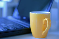 Gele koffiemok en laptop stock foto