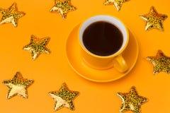 Gele kop met zwarte koffie op een gele achtergrond, gouden sterren rond een kop Royalty-vrije Stock Foto's
