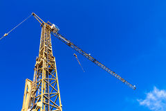 Gele kraan op een bouwwerf met blauwe hemel Stock Foto's