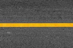 Gele lijn op de wegachtergrond van de asfalttextuur met korrelig stock afbeeldingen