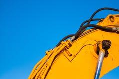 Gele machines en hydraulica op blauwe hemel stock afbeelding