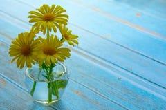Gele madeliefjes in een vaas op een blauwe houten lijst, Exemplaarruimte stock fotografie