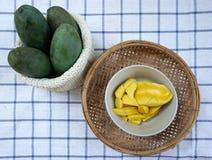 Gele mango's klaar om met groene mango'sachtergrond te eten Royalty-vrije Stock Afbeelding