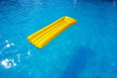 Gele matras in de pool Stock Foto