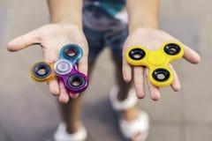 Gele meisjes de holding en de regenboog friemelen hierboven spinners in haar handen, mening van stock afbeelding
