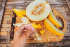 Gele meloenplakken met vormhart in vrouwelijke hand Royalty-vrije Stock Foto