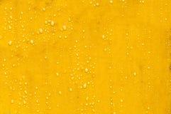 Gele metaaloppervlakte met condensatiedalingen op de oppervlakte Macrowijze royalty-vrije stock foto