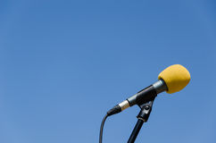 Gele microfoon blauwe hemel bakcground Stock Afbeeldingen