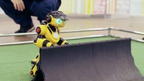 Gele moderne robot bij de tentoonstelling van nieuwe technologie?n De mens controleert de robot stock videobeelden