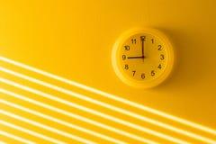Gele muur & klok stock afbeeldingen