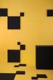 Gele muur en vloer met zwarte vierkanten en zwarte doos Royalty-vrije Stock Afbeeldingen