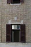 Gele muur van de oude bouw met bruine blinden op vensters Royalty-vrije Stock Fotografie