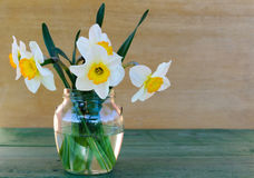 Gele narcissen in een glasvaas op houten achtergrond royalty-vrije stock afbeelding