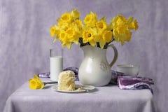 Gele narcissen, melk en cake Royalty-vrije Stock Afbeelding
