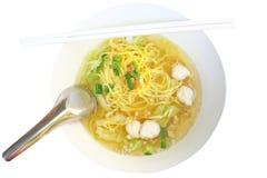 Gele noedels en vissenbal in duidelijke soep stock afbeelding