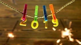 Gele nummer 2019 die op een wasknijper op een kabel op een houten achtergrond, close-up, Nieuwjaar 2019, Kerstmis hangen, zij stock video