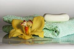 Gele orchidee met handdoek en zeep op de witte achtergrond - wellness Royalty-vrije Stock Afbeelding