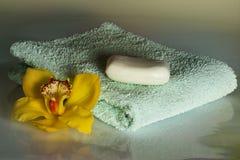Gele orchidee met handdoek en zeep op de witte achtergrond - wellness Stock Afbeeldingen