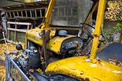 Gele oude tractor binnen Stock Foto