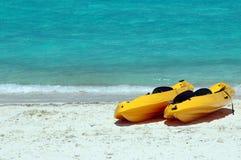Gele overzeese kajaks op het strand Stock Foto's