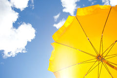 Gele paraplu op blauwe hemel met wolken Royalty-vrije Stock Foto