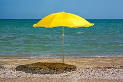Gele paraplu op een verlaten zonnig zandig strand op de achtergrond van het overzees Royalty-vrije Stock Foto