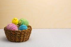 Gele Pasen-kuiken en mand van paaseieren Stock Foto