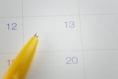 gele penpunten aan aantal 13 op kalenderachtergrond Royalty-vrije Stock Afbeeldingen