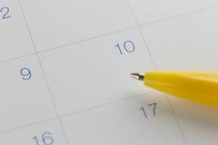gele penpunten aan aantal 10 op kalenderachtergrond Royalty-vrije Stock Afbeeldingen