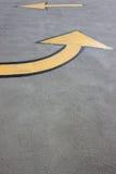 Gele pijlen op asfalt Stock Foto's