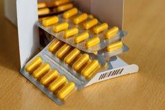 Gele pillen in een blaarpak op de lijst Stock Fotografie