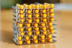 Gele pillen in een blaarpak op een houten lijst Stock Afbeelding