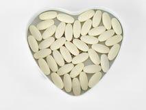 Gele pillen in een hart-vormige die doos, op de witte achtergrond wordt geïsoleerd Royalty-vrije Stock Fotografie
