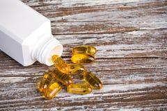Gele pillen met witte plastic container Royalty-vrije Stock Foto's