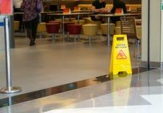 Gele plastic kegel met teken die waarschuwing van natte vloer in reyellow plastic kegel tonen met teken die waarschuwing van natt stock foto