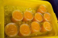 Gele plastic ton met water en ijs die negen duidelijk plastic koppenhoogtepunt van jus d'orange houden De koppen hebben duidelijk stock afbeeldingen