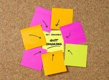 Gele post-itnota over cork raad en tellerspijl als herinnering van het opgehouden met roken Stock Foto