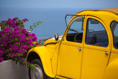 Gele retro auto en de zomerbloemen. Stock Foto's
