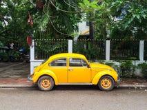 Gele retro auto op de straat van Vientiane Royalty-vrije Stock Foto's