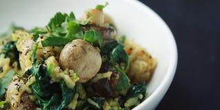 Gele rijst met paddestoelen en spinazie Veganistschotel royalty-vrije stock foto