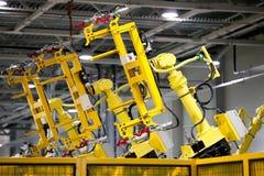 Gele robots op een lopende band stock fotografie