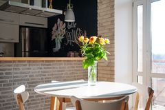 Gele rozen in een glasvaas op de lijst Vakantie en vieringsconcept royalty-vrije stock fotografie