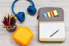 Gele sandwichdoos, metaaltribune met kleurenpotloden, hoofdtelefoons Stock Foto