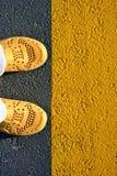 Gele schoenen op het asfalt, een stap in de toekomst royalty-vrije stock afbeelding