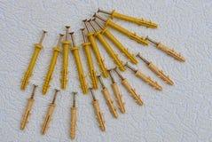 Gele schroeven en pennen in een stapel op een grijze lijst Royalty-vrije Stock Afbeeldingen