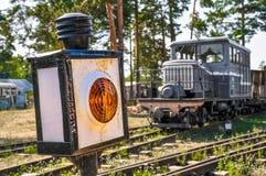 Gele seinpaal en de locomotief op de spoorweg Stock Afbeelding