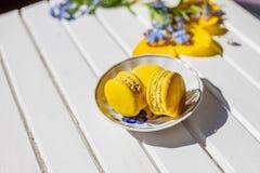 Gele smakelijke macaronikoekjes op de plaat Suikergoedbar Kinderen` s verjaardag Frans dessert op witte houten achtergrond Stock Afbeeldingen