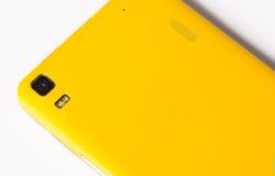 Gele smartphone op een witte achtergrond Stock Fotografie