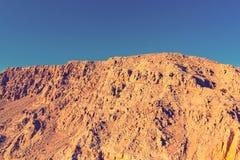Gele steile hellingen tegen de blauwe hemel op de kust van het Arabische Overzees royalty-vrije stock afbeelding