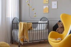 Gele stoel en, bruine teddybeer en grijze houten voederbak met deken in elegante babyslaapkamer royalty-vrije stock foto